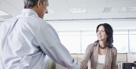 Man and woman shaking hands in office --- Image by © Monalyn Gracia/Corbis