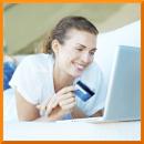 Frau schaut auf Laptop mit Karte in der Hand