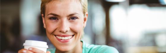Frau lächelt mit Kaffee in der Hand