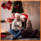 Päarchen, Weihnachten, Geschenke, Weihnachtsgeschenke, Nikolausmützen, Umarmung, Weihnachtsmannsocke, Teppich, geschmückter Tannenbaum, Lächeln, Lichterketten