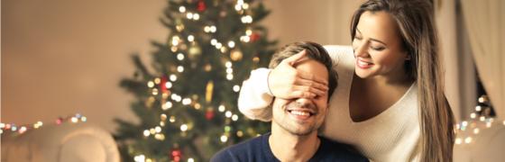 Päarchen, Weihnachten, Geschenke, Weihnachtsgeschenke, geschmückter Tannenbaum, sie hält ihm die Augen zu, Lächeln, Lichterketten