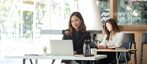 Frau sitzt im Büro mit Laptop und lächelt