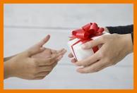 Hand übergibt Geschenk an andere Hand